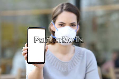 woman with mask showing phone with