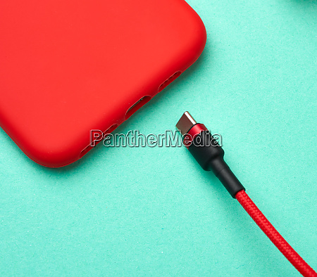 red smartphone and cable in textile