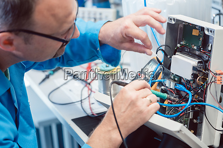 electronics engineer troubleshooting defects in a