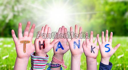 children hands building word thanks grass