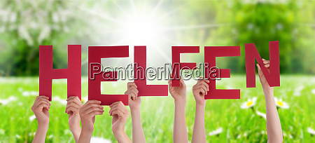 people hands holding word helfen means