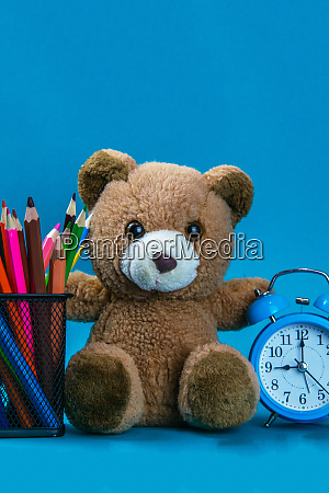 blue alarm clock with brown bear