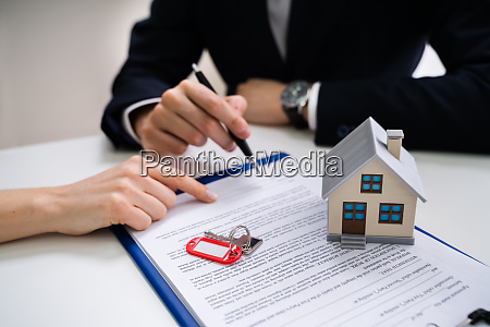 persons hand signing contract with keys