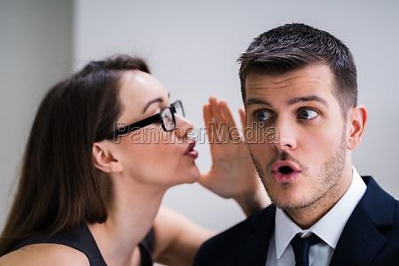 businesswoman whispering into male partners ear