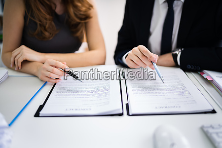 two businesspeople working on contract paper