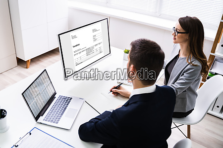 two businesspeople analyzing invoice
