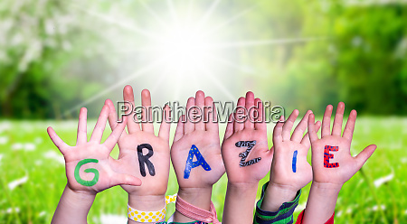 children hands building word grazie means