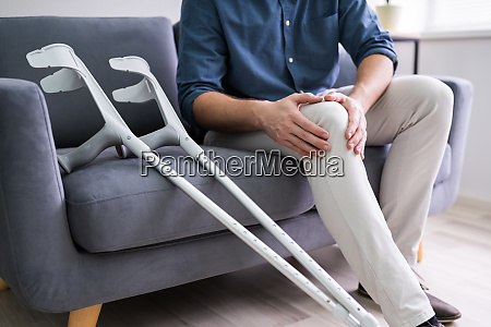 man suffering from knee pain sitting