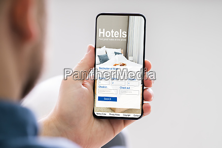 person booking hotels using cell phone