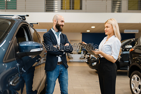 smiling man and saleswoman in car