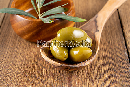 green olives on a wooden cooking