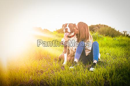 beatiful young woman kissing dog in