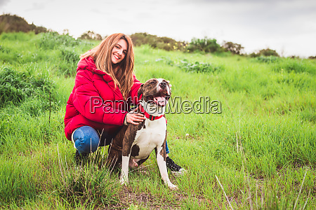 young woman sitting with american staffordshire