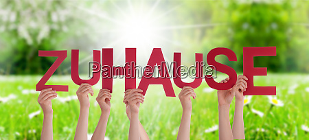 people hands holding word zuhause means