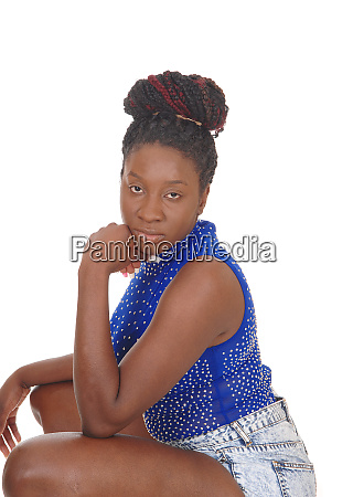 serious looking african woman crouching on