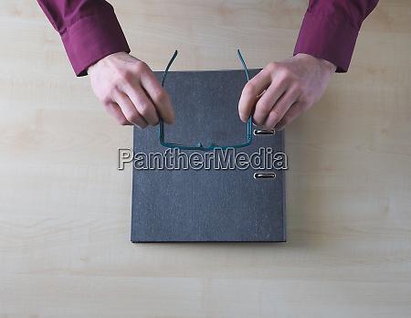 writing desk file folder hands glasses