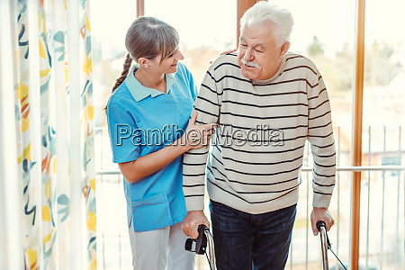 nurse helping senior man with walking