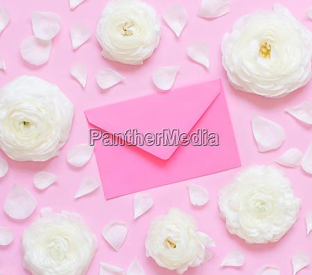 cream ranunculus flowers and envelope on
