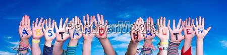 children hands building word abstand halten