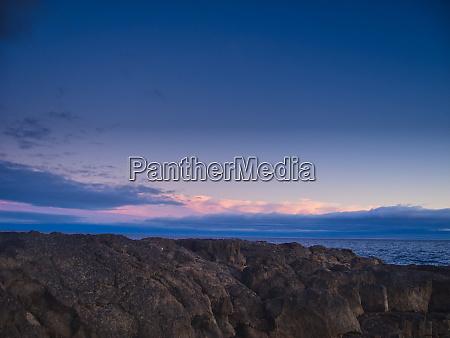 sunset rocks and a light sky