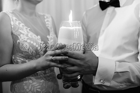 groom puts bride on wedding candle