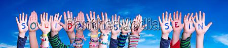 kids hands holding word solidarisch sein
