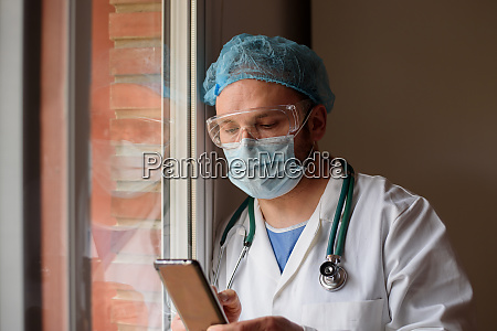 doctor in face mask using smartphone