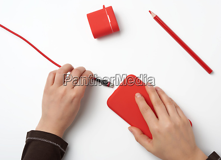 two hands holding a red mobile