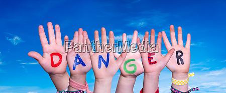 children hands building word danger blue