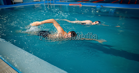 male and female swimmers swims in