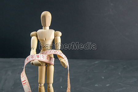 wood figure mannequin with measuring tape