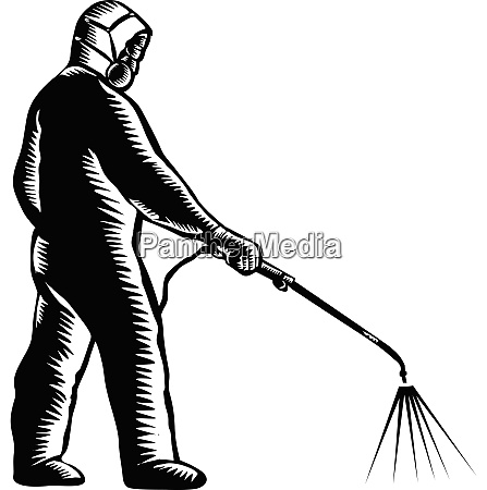 essential worker wearing ppe spraying disinfectant