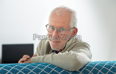 senior with grey hairs wearing eyeglasses