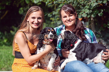 two girlfriends having fun with dogs