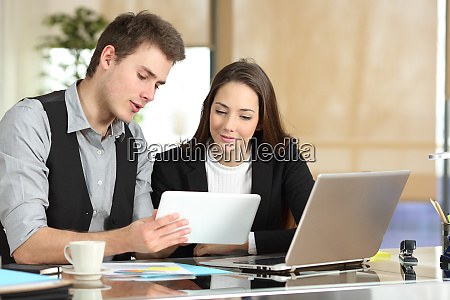 employee helping coworker showing tablet