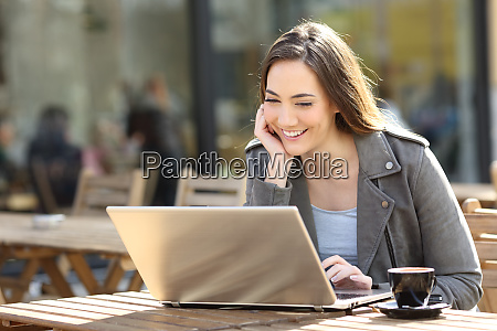happy, woman, watching, media, on, laptop - 28277950