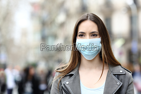 serious woman with mask looking away
