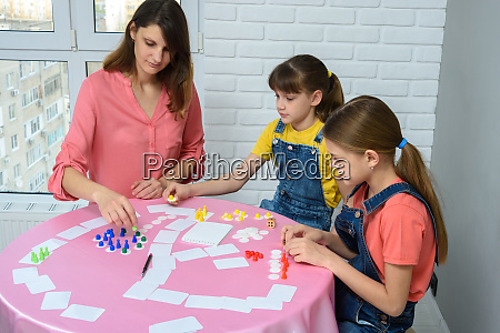 mom and two daughters play board