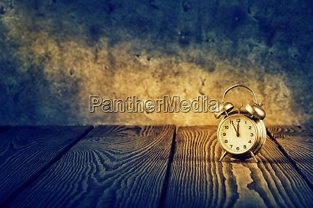old alarm clock under beam of