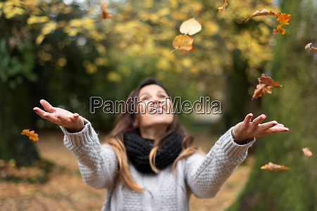 happy woman throwing leaves in autumn