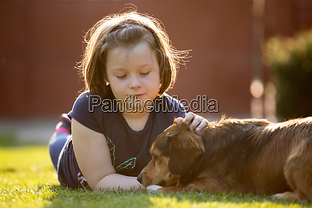kid playing with cute little dog