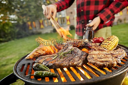 man holding a beer grilling meat