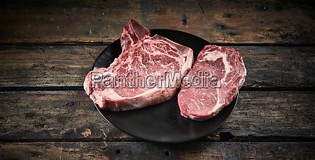 two portions of raw ribeye steak