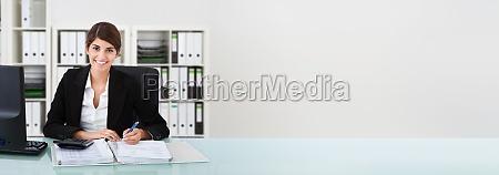 female accountant writing on documents