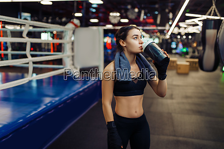 woman in boxing bandages drinks water