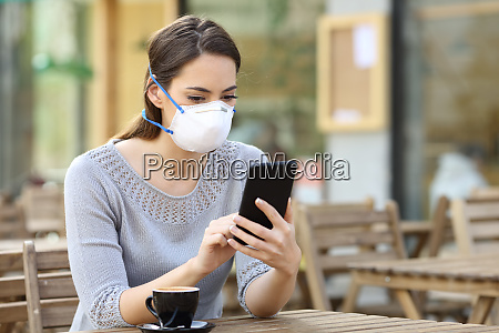 woman with mask checking news on