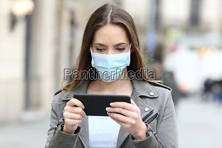 woman with mask watching video on