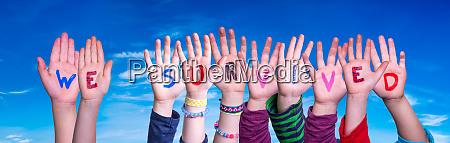 children hands building word we survived