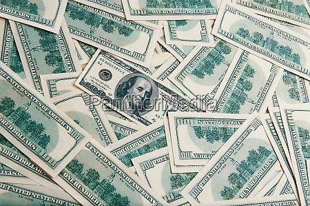 a background of scattered hundred dollar