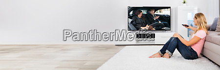 woman sitting on carpet watching television